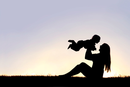 A silhouette of a happy, laughing mom sitting in the grass at sunset, lifting her baby boy up into the air.